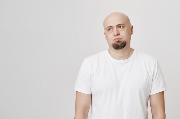 Homem careca cansado a suspirar e desviar o olhar relutante