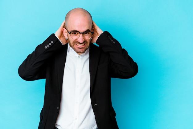 Homem careca caucasiano de negócios jovem isolado em um fundo azul, tocando a parte de trás da cabeça, pensando e fazendo uma escolha.