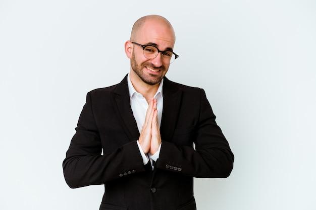 Homem careca caucasiano de negócios jovem isolado na parede azul, de mãos dadas para orar perto da boca, sente-se confiante.