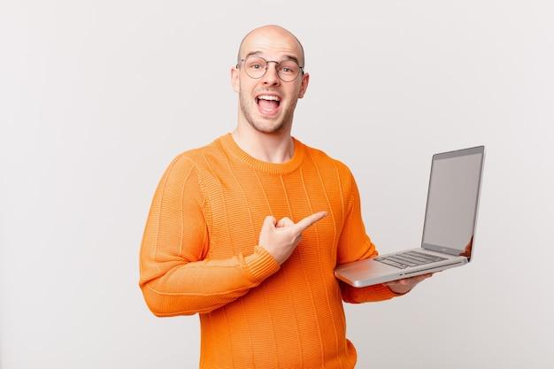 Homem careca com computador parecendo animado e surpreso apontando para o lado e para cima para copiar o espaço