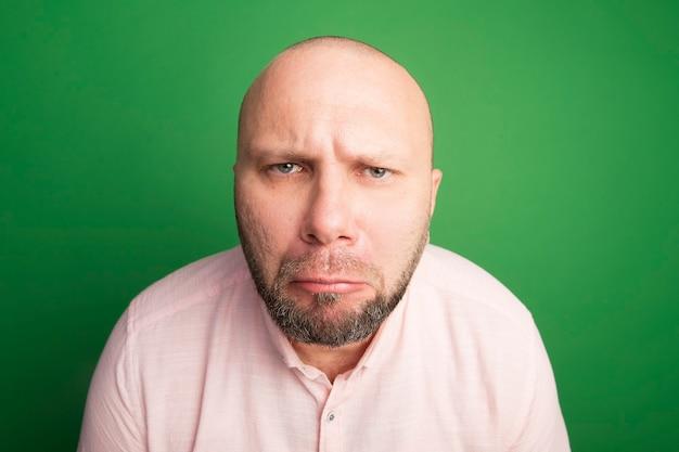 Homem careca de meia-idade com ar insatisfeito e camiseta rosa