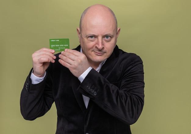 Homem careca de meia-idade em terno mostrando cartão de crédito sorrindo maliciosamente em pé sobre uma parede verde