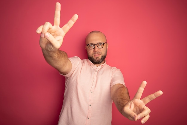 Homem careca de meia-idade satisfeito com uma camiseta rosa e óculos mostrando um gesto de paz isolado em rosa