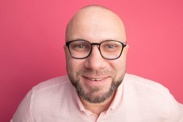 Homem careca de meia-idade sorridente com camiseta rosa e óculos