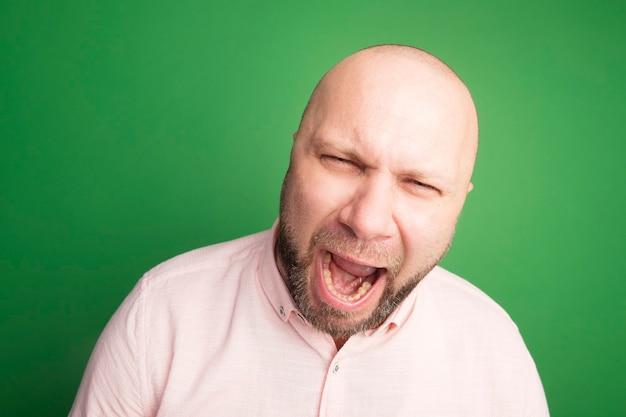 Homem careca de meia-idade zangado com camiseta rosa