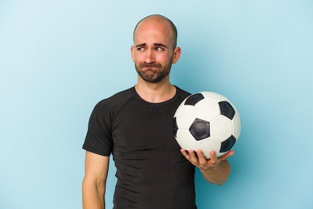 Homem careca de negócios jovem jogando futebol isolado em um fundo azul confuso, sente-se em dúvida e inseguro.