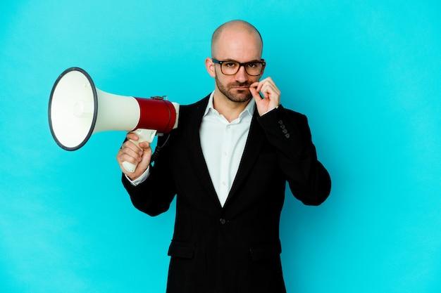 Homem careca de negócios jovem segurando um megafone isolado com os dedos nos lábios, mantendo um segredo.
