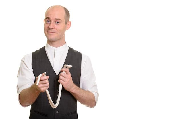 Homem careca e mágico, segurando uma corda para um truque de mágica