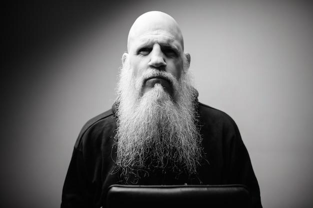 Homem careca maduro com longa barba grisalha contra parede branca em preto e branco