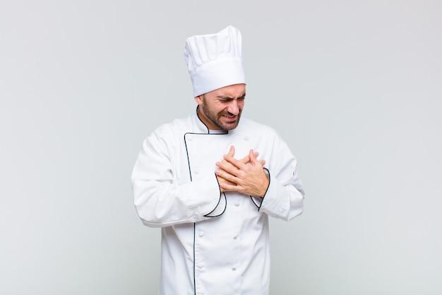 Homem careca parecendo triste, magoado e com o coração partido, segurando as duas mãos perto do coração, chorando e se sentindo deprimido