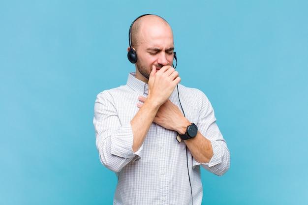 Homem careca sentindo-se mal com dor de garganta e sintomas de gripe, tosse com a boca coberta