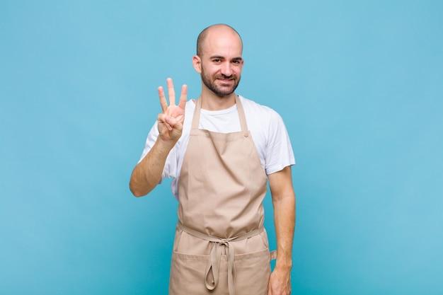 Homem careca sorrindo e parecendo amigável, mostrando o número três ou terceiro com a mão para a frente, em contagem regressiva