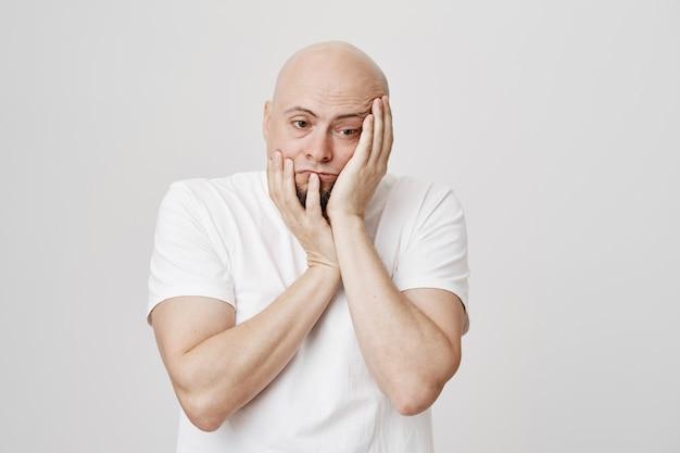 Homem careca triste e angustiado de mãos dadas no rosto e desviar o olhar