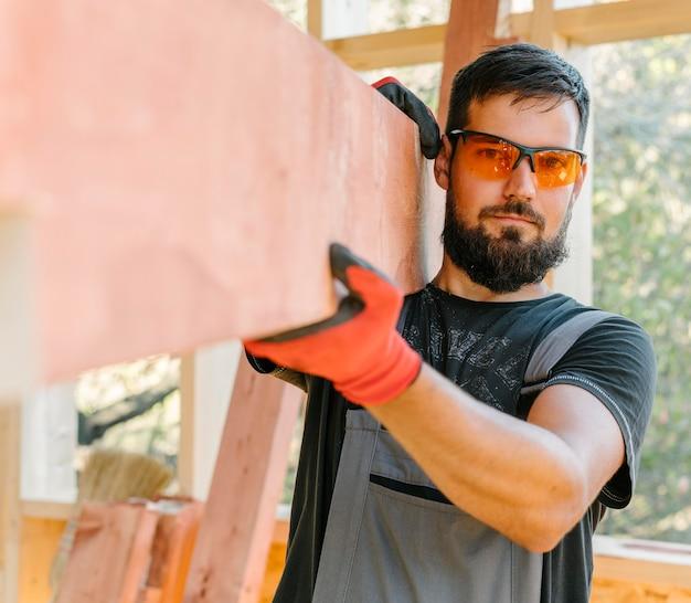 Homem carpinteiro com óculos de proteção, vista frontal