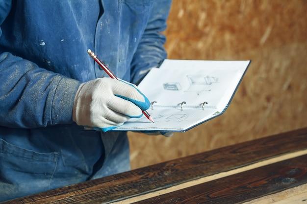 Homem carpinteiro em seu estúdio caseiro trabalhando com madeira e desenhando esboços a lápis em um caderno