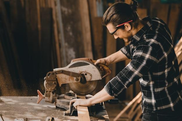 Homem carpinteiro usando woodcraft electric wood cutter trabalhando na oficina de madeira de móveis com habilidade profissional workman.image reais contêm ruído de poeira.