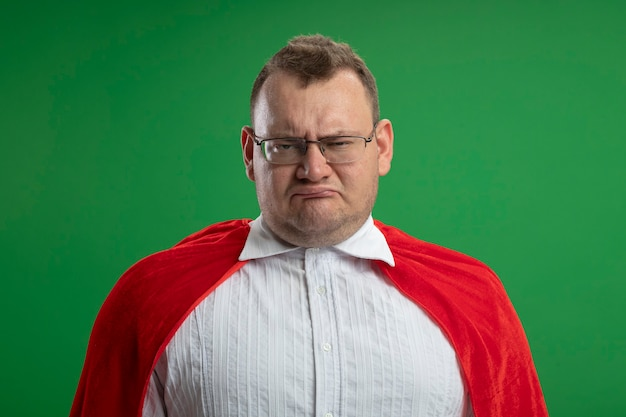 Homem carrancudo super-herói eslavo adulto com capa vermelha e óculos isolados na parede verde