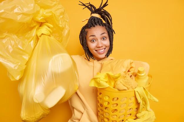 Homem carrega cesto de roupa suja satisfeito com os resultados da limpeza da casa usa moletom com luvas de proteção de borracha isoladas no amarelo