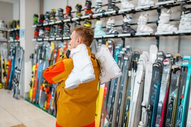 Homem carrega no ombro botas de esqui ou snowboard na loja de esportes.