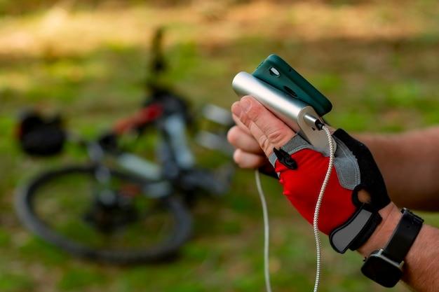 Homem carrega um smartphone com um banco de energia no fundo de uma bicicleta na floresta.