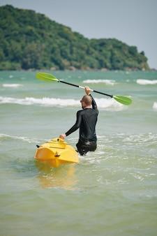 Homem carregando barco caiaque