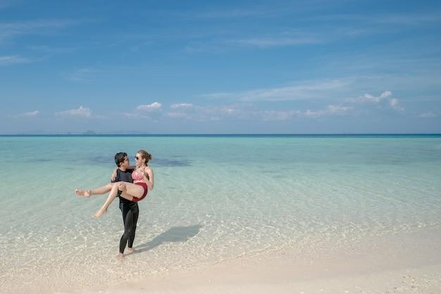Homem carregando mulher de biquíni na água do mar pela praia de areia branca. paisagem azul do mar e do céu. férias de verão.