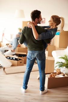 Homem carregando namorada na nova casa