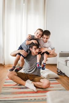 Homem carregando seus dois filhos no ombro