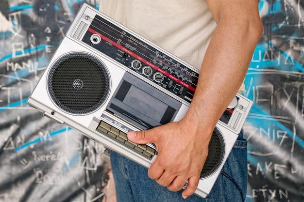 Homem carregando um boombox vintage próximo a uma parede com grafite