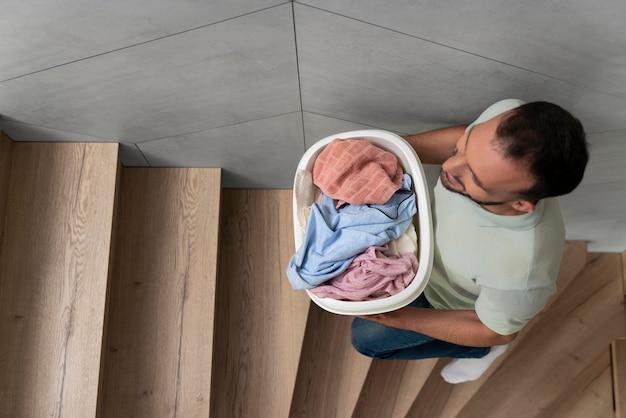 Homem carregando um monte de roupas sujas na cesta