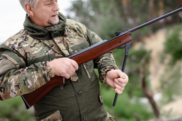 Homem carregando um rifle de caça na floresta de verão.