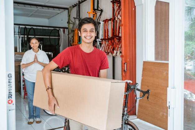 Homem carregando uma grande caixa de bicicletas desmontadas enquanto compra uma bicicleta nova