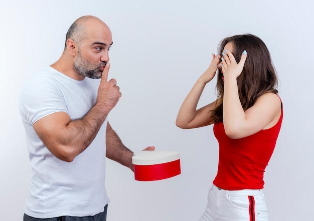 Homem casal adulto impressionado segurando uma caixa de presente em forma de coração, olhando para a mulher e fazendo o gesto de silêncio, mulher mantendo as mãos perto dos olhos em pé com os olhos fechados