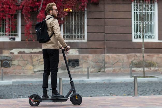 Homem casual andando com sua scooter elétrica