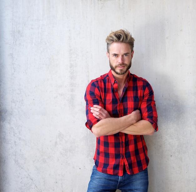 Homem casual bonito com barba posando com os braços cruzados