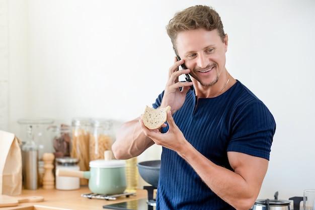 Homem casual comendo pão como café da manhã e falando no celular em casa
