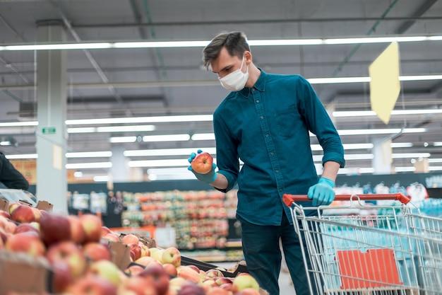 Homem casual comprando frutas no período de quarentena. conceito de segurança