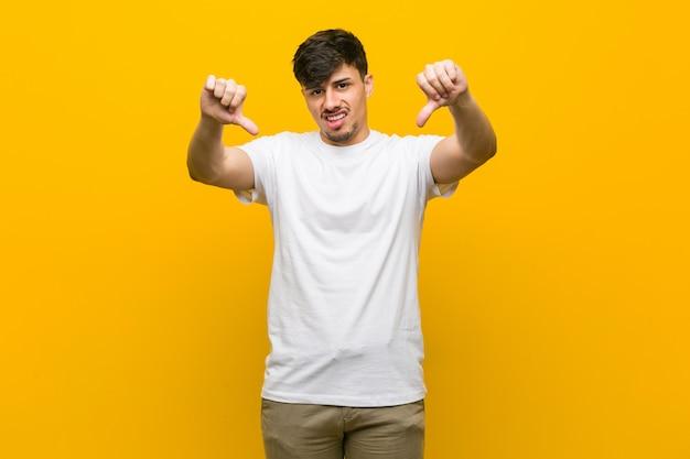 Homem casual latino-americano novo que mostra o polegar para baixo e que expressa a antipatia.
