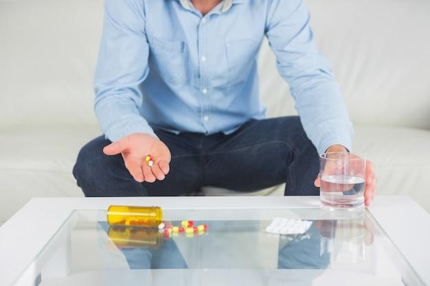 Homem casual mostrando pílulas na mão aberta
