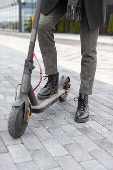 Homem casual posando com sua scooter elétrica