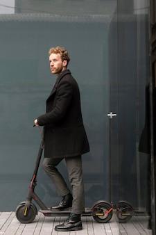 Homem casual posando com uma scooter elétrica