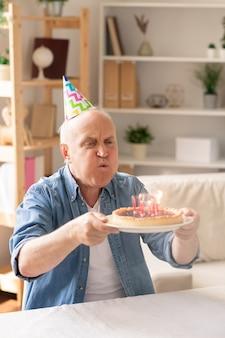 Homem casual sênior segurando o prato com bolo de aniversário na frente dele e soprando velas