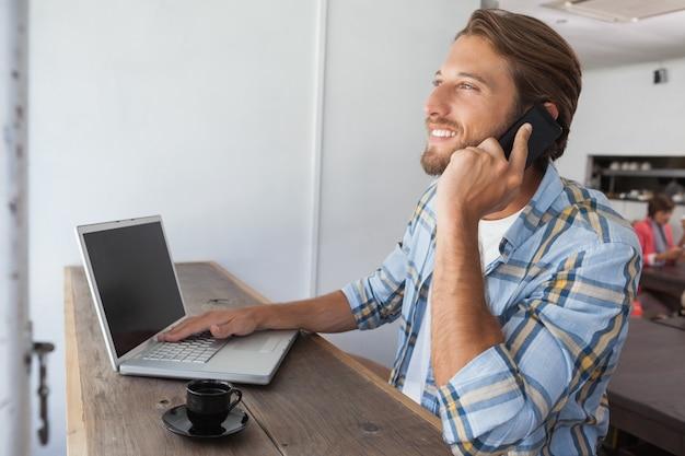 Homem casual usando um laptop com café