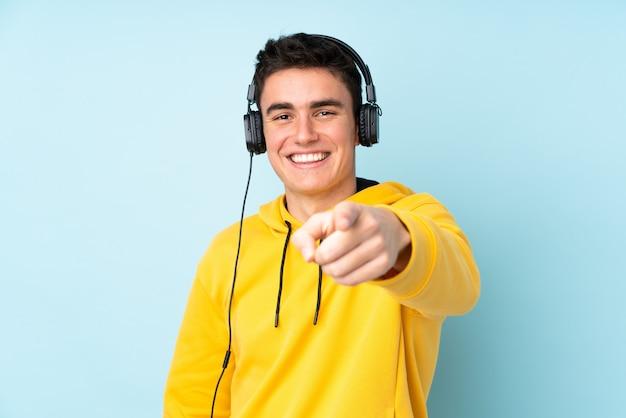 Homem caucasiano adolescente isolado na música roxa e apontando para a frente