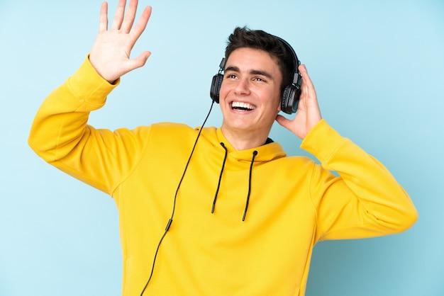 Homem caucasiano adolescente isolado no fundo roxo, ouvir música e dançar