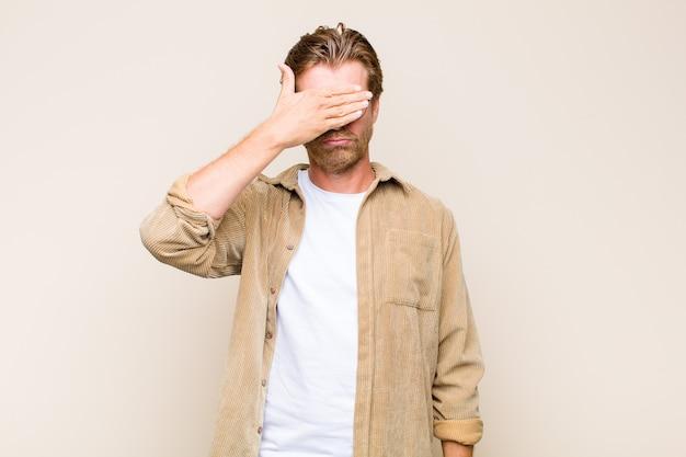 Homem caucasiano adulto loiro cobrindo os olhos com uma mão, sentindo-se assustado ou ansioso, imaginando ou esperando cegamente por uma surpresa