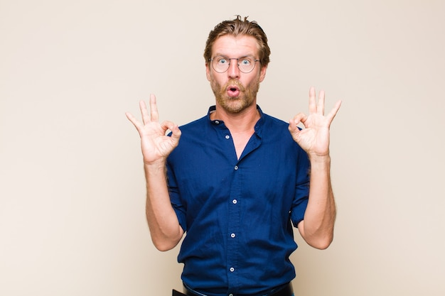 Homem caucasiano adulto loiro se sentindo chocado, espantado e surpreso, mostrando aprovação e fazendo sinal de ok com as duas mãos