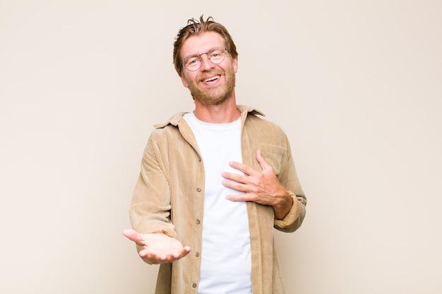 Homem caucasiano adulto loiro se sentindo feliz e apaixonado, sorrindo com uma mão ao lado do coração e a outra esticada na frente