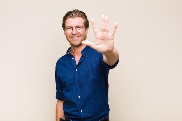 Homem caucasiano adulto loiro sorrindo e parecendo amigável, mostrando o número cinco ou quinto com a mão para a frente, em contagem regressiva