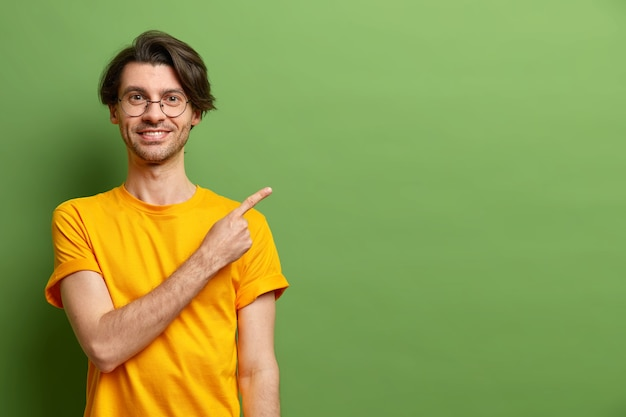 Homem caucasiano alegre aponta o dedo indicador para o espaço da cópia e sugere oferta especial